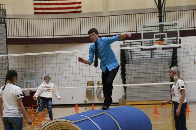 STEADY AS HE GOES: Senior Bryson Jenkins navigates the obstacle course to win the seniors a long lunch during the cross country state send off.