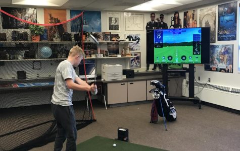 SHAKING THE RUST OFF: Junior Karsen Spaulding takes a practice swing before hitting the ball in Coach Fullmer's room earlier this February.