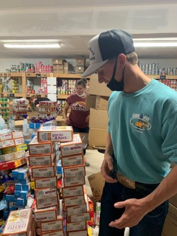 "WORKING HARD OR HARDLY WORKING: Cody Gustafson ""helps"" stack crackers on the shelf. He says, ""McKay is dope, and i like to get out of class to do service."""