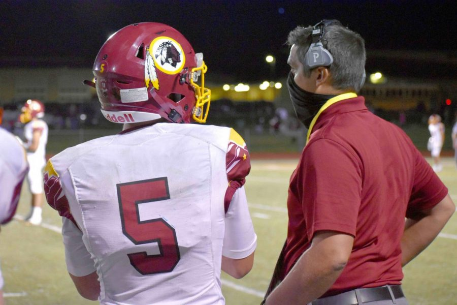 MASKED+MAN%3A+Coach+Young+speaks+through+his+mask+to+quarterback+Brant+Nelson.