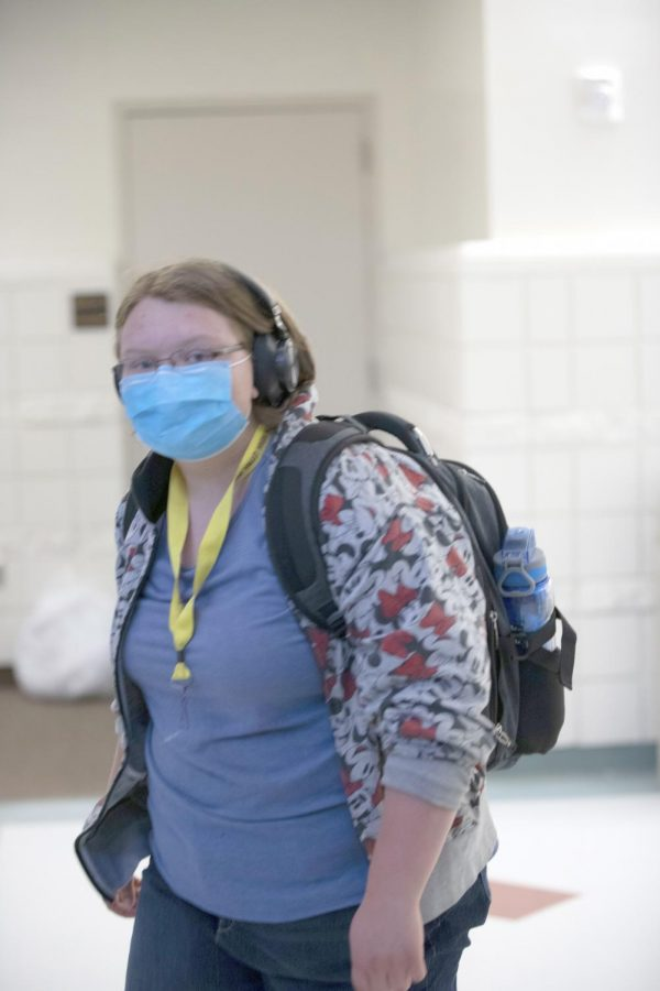 TUNED OUT: Freshman Genevieve Goodson accessorizes with two student staples: mask and headphones.