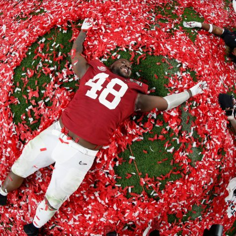 CONFETTI ANGEL: Number 48 takes in the moment and enjoys it by doing a snow angel in all the confetti.