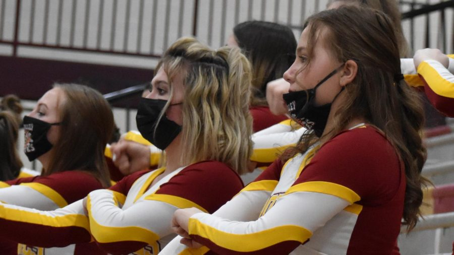 CHEER UP: Junior Karlee Cassidy and sophomores Auderie Hansen and Bently Bowcut show their sprit and social responsibility while repping the masks  and cheering for the Braves.