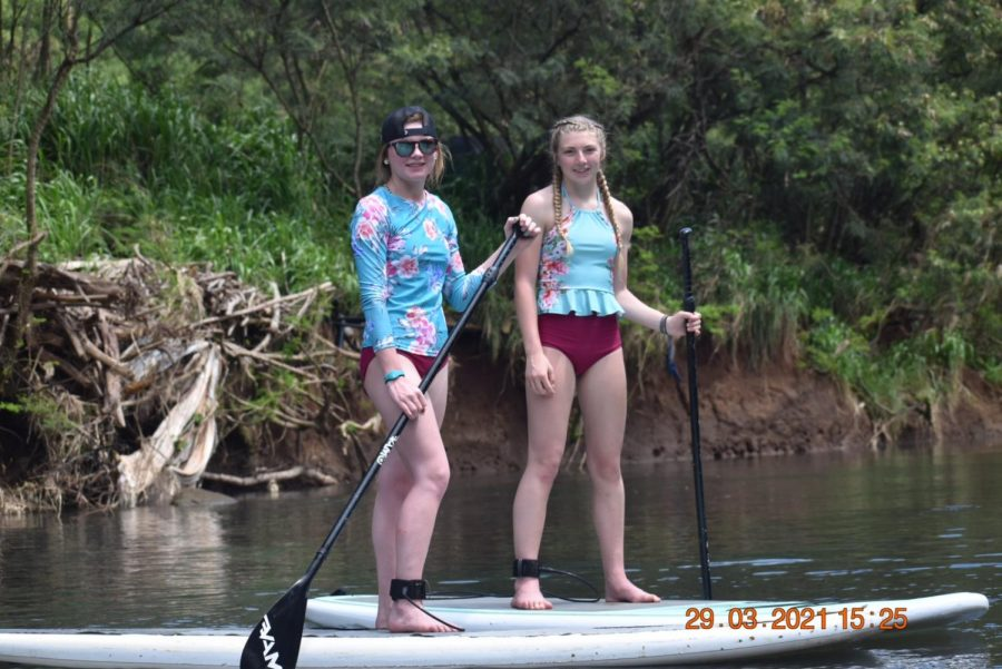 FLOAT%27N+THE+RIVER%3A+Maddie+Hale+and+her+sister+Caellie++Hale+balance+on+a+paddle+board+in+Hawaii.+%E2%80%9CWe+had+lots+of+fun+experiences.+We+hiked+to+a+few+different+waterfalls%2C+and+we+even+got+to+swim+under+them.+My+favorite+thing+we+did+was+probably+paddle+boarding+in+the+river+with+all+the+turtles.+The+pineapple%2C+donuts+and+the+snow+cones+were+amazing%2C%22+said+Maddie.