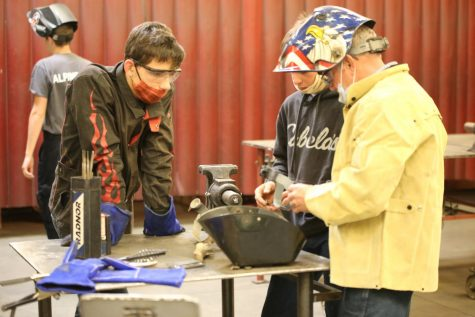 "LET ME SHOW YOU: Mr. Warren doing what he has done for 30 years, helping kids like Josh Baird learn tradecraft. ""Welding has also played a major role in my teaching, and I still get excited when I see the look on a student's face that says,"