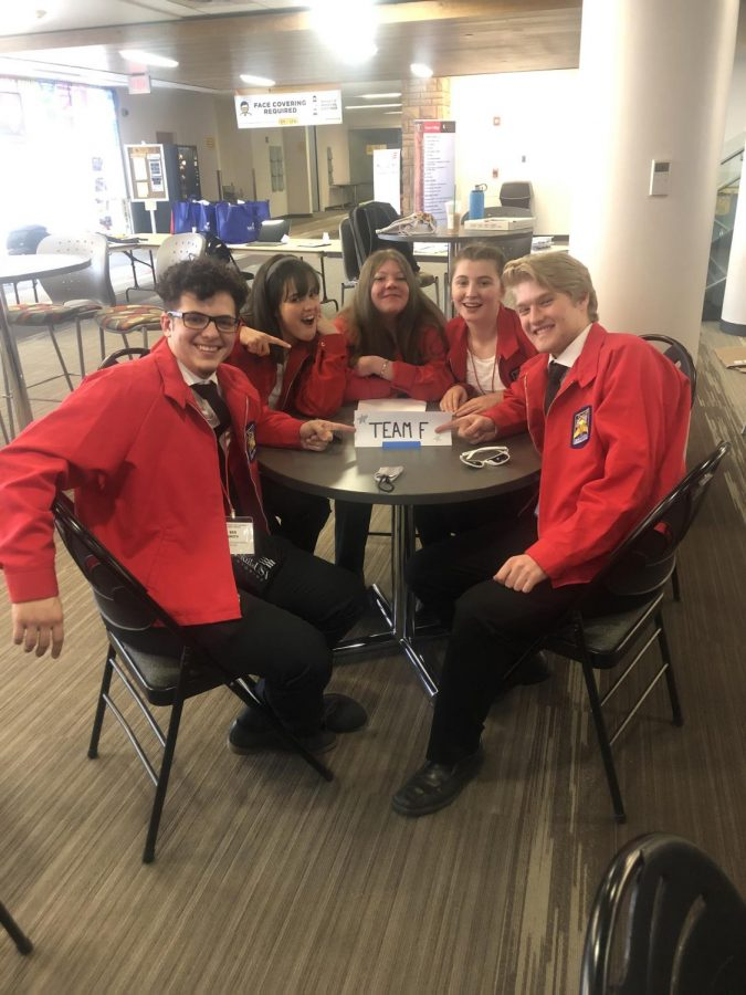 """SKILLS USA: Skills USA members gather around a table in their matching jackets. Skills is a club open to anyone who wants to compete career skills-based competitions. """"Skills USA is always a lot of fun,"""
