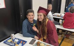 LUNCH DATE: NHS member Emma Thomson visits with a young Osmond Elementary student.