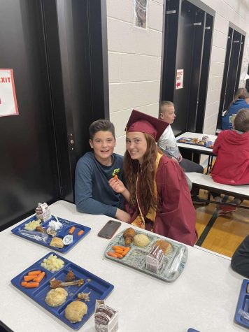 """LUNCH DATE: NHS member Emma Thomson visits with a young Osmond Elementary student. """"I was proud to represent what these kids can eventually achieve if they work hard and stay in school,"""" said Thomson."""