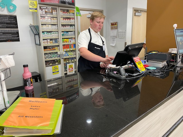 CHECKING OUT: Senior Daxon Gilbert checks a customer out at the front desk in Broulims. Balancing a schedule can be quite the task with a job and school.