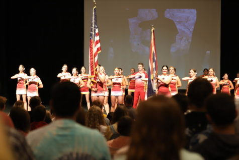 ALL RISE: The cheer squad leads the student body in the Pledge of Allegiance to kick off the first assembly of the school year.