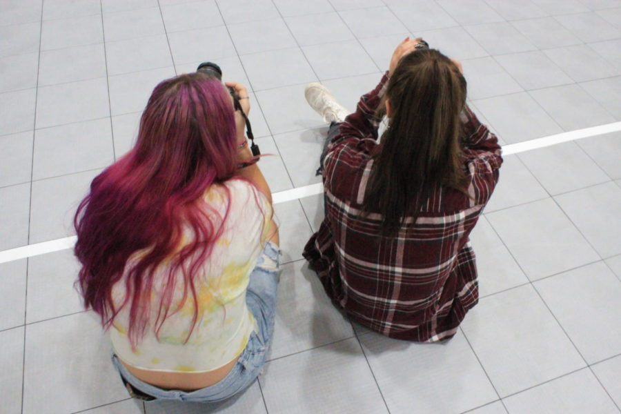 BACK IT UP: Lilly Fisher and Joy Fry scan the horizon for possible subject to photograph. Some students like them have express frustration over the current dress code and how it is enforced.