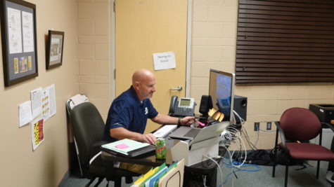 HARD AT WORK: Compliance Facilitator Mr. Brian Toomer sits at his at desk determined to  finish all of his work. Toomer started here after serving as principal at Cokeville High School. Outside of school, I really enjoy all the sports this school provides, said Toomer.